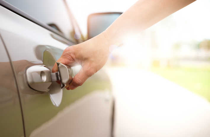 Photo of a woman's hand opening a car door